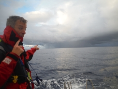 Andy Royse points out a tropical rain storm in the doldrums. These came fast and provided a good showering opportunity (after a few reefs had been put in)